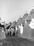 Row of Trulli Homes Made from Limestone Boulders and Feature Conical or Domed Roofs Photographic Print by Alfred Eisenstaedt