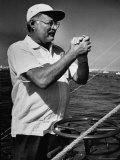 Author Ernest Hemingway at Wheel of Fishing Boat During Fishing Tournament Kunst op metaal van Alfred Eisenstaedt
