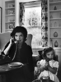Jackie Kennedy, Wife of Senator John Kennedy, Talking on the Telephone as her daughter mimics her Photographic Print by Alfred Eisenstaedt