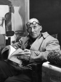 Architect Le Corbusier Sitting in Chair and Holding Book in Hands Reproduction photographique sur papier de qualité par Nina Leen