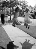 Girls on the street in neighborhood using rope to jump in tandem while man with toddler watches Premium Photographic Print by Alfred Eisenstaedt