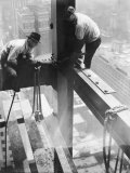 Workers balancing on steel beam above streets during construction of the Manhattan Company Building Premium Photographic Print by Arthur Gerlach