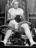 Pat Ogden at Slenderizing Salon Knitting in Padded Chair While Leg Rollers Work from Thigh to Ankle Premium Photographic Print by Alfred Eisenstaedt