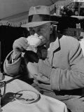 Syndicated Columnist Walter Winchell Clad in Overcoat and Gloves Drinking Coffee in Outdoor Patio Premium Photographic Print by Alfred Eisenstaedt