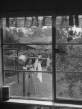 Suburban Housewife Hanging Out a Bit of Laundry, Seen Through Window in typical California Home Photographic Print by Loomis Dean