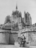 American Travelers Below France's Medieval Abbey at Mont Saint Michel Reading Together from a Book Photographic Print by Yale Joel