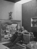 Architect Le Corbusier Sitting in Chair with Book in Hands, Glasses Perched on His Forehead Premium Photographic Print by Nina Leen