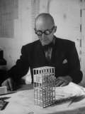 Architect Le Corbusier Studying Architectural Plans and Small Model of Building in His Office Premium Photographic Print by Nina Leen