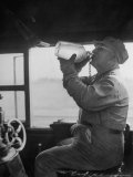 Engineer in the 20th Century Limited Drinking Water from Glass Jug He Kept Underneath His Stool Photographic Print by Alfred Eisenstaedt