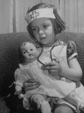 Evelyn Mott playing Nurse with doll as parents adjust children to abnormal conditions in wartime Photographic Print by Alfred Eisenstaedt