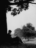 British Author Colin Wilson Sitting Underneath a Tree Wrapped in a Sleeping Bag, Reading a Book Premium Photographic Print by Mark Kauffman