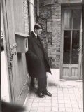 Christian Dior's Successor Yves Saint Laurent Standing Alone After Attending Dior's Funeral Reproduction photographique sur papier de qualité par Loomis Dean