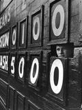 Boy Running Scoreboard at Griffith Stadium During the Baseball Game Photographie par Hank Walker