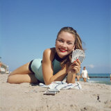Model Holding Hand of Playing Cards While Relaxing on Beach Photographic Print by Hank Walker