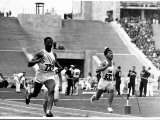 Metcalfe of US at the Finish Line of the Seventh Heat of the 100 Meter Race at the Summer Olympics Premium Photographic Print