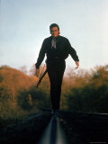 Country Music Star Johnny Cash Walking Along Line of Railway Track with His Guitar Metalldrucke von Michael Rougier