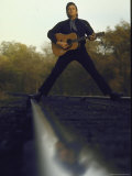Country/Western Singer Johnny Cash with Guitar Straddling Railroad Tracks Premium Photographic Print by Michael Rougier
