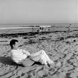 Designer Charles Eames Sitting on a Beach Near His Home Premium Photographic Print by Peter Stackpole