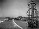 Overview Seaside Amusement Park, Waders in Ocean, Rollercoasters and Activity Centers on Boardwalk Premium Photographic Print by Henry G. Peabody