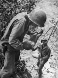 American Lieutenant Carrying Micronesian Baby He Found in cave Japanese Soldiers Holed Up There Premium Photographic Print by W. Eugene Smith