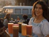 Kellnerin trägt ein Tablett mit Säften aus Karotten, Sellerie, roter Beete, Orangen, Äpfeln und Grapefruit Premium-Fotodruck von Michael Rougier