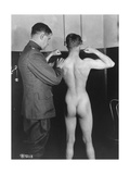 WWI Aviation Recruit Flexing Muscles for Military Doctor While Standing Naked in Examination Room Premium Photographic Print by Lt. Reid