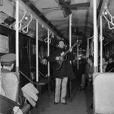 Activist Folk Musician Woody Guthrie Playing for a Subway Car of New Yorkers Premium Photographic Print by Eric Schaal