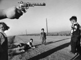"Boy's Hand Holding a Toy Six Shooter Pistol During a Game of ""Cops and Robbers"" Premium Photographic Print by Howard Sochurek"