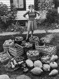 Woman Looking at Victory Garden Harvest Sitting on Lawn, Waiting to Be Stored Away for Winter Papier Photo par Walter Sanders