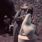 French Sculptor Jean Arp, Alone, Polishing Abstract Sculpture in His Garden Near Paris Premium-Fotodruck von Gjon Mili