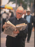 Episcopalian Priest Reading a Newspaper While Walking in Street, New York City Premium Photographic Print by Vernon Merritt III