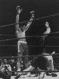 Boxer Muhammad Ali Raising His Gloves Victoriously After Knocking Out Oscar Bonavena Premium Photographic Print by Bill Ray