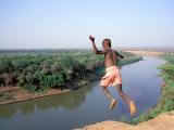Karo Boy Leaps Off a Cliff Over the Omo River, Ethiopia Fotografisk tryk af Janis Miglavs