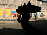 A Boy Carrying Bottles on His Head Passes by a Wall with Pictures of Haitian President Renel Preval Lmina fotogrfica por Ariana Cubillos