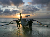Balinese Fishermen Push Their Boat to Land During Sunset at a Beach Photographic Print