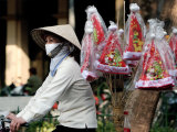 A Vietnamese Vendor Rides Downs a Hanoi City Street Selling Santa Hats Photographic Print