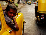 Taxi Driver Leaning Out Window As Motor Rickshaw Goes Past, Chowringee, India Lmina fotogrfica por Anthony Plummer