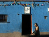 An Aymara Woman Walks Past the Only Telephone in the Village of Curahuara De Carangas Photographic Print