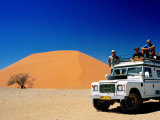 Men on Four Wheel Drive Vehicle at Dune 45 in Namib Nauklaft National Park, Sossusvlei, Namibia Fotografiskt tryck av Christer Fredriksson