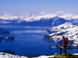 Hiker Overlooking Lake with Mountains in Distance, Prince William Sound, U.S.A. Photographic Print by Mark Newman
