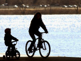 A Mother and Son are Silhouetted as They Ride Along the Schuylkill River Photographic Print