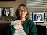 A Female Wears Circuit Glasses in Front of Two Computer Monitors Photographic Print by Joel Sartore