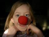 A Young Female Sports a Bright Red Clown Nose Photographic Print by Joel Sartore