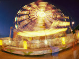 A Slow Exposure Captures Lights on a Spinning Carnival Ride Photographic Print by Heather Perry