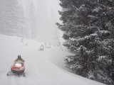 A Group of Snowmobilers Turn a Corner in a Snowstorm Photographic Print by Taylor S. Kennedy