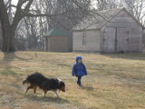 A Young Male and His Sheltie Dog Walk Through a Historic Farm Photographic Print by Joel Sartore