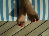 Woman's Feet on a Striped Cushion on the Deck of a Cruise Ship Photographic Print by Todd Gipstein