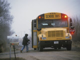 A Student Boards a School Bus in the Morning Fog Photographic Print by Joel Sartore