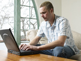 Male Young Adult Sitting on Couch Using Laptop Computer Photographic Print