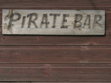 A Wooden Wall with a Wooden Sign for a Pirate Bar Lámina fotográfica